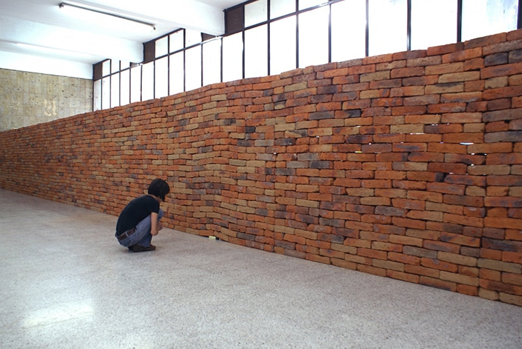 Installation Reveals the Metaphoric Power of a Single Book Distorting a Solid Brick Wall